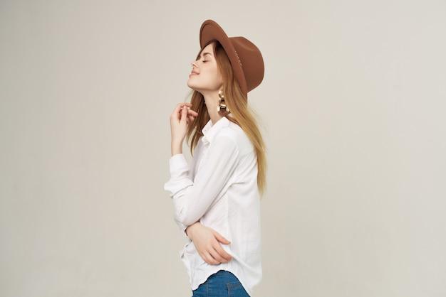 Mulher atraente usando chapéu camisa branca estilo de vida moda luxo posando
