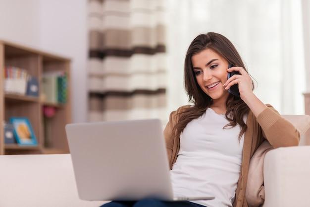 Mulher atraente usando laptop e smartphone em casa