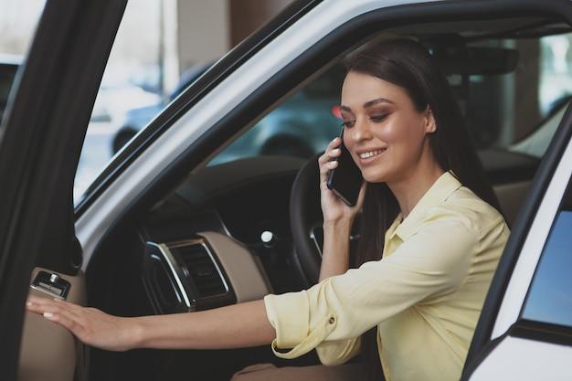 Mulher atraente usando seu telefone inteligente enquanto bying carro novo