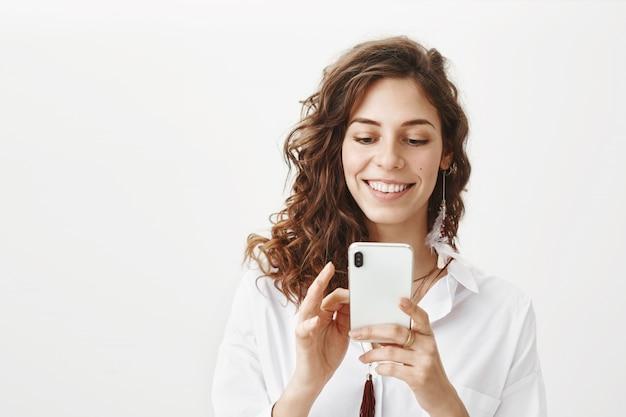 Mulher atraente usando telefone celular, baixar aplicativo