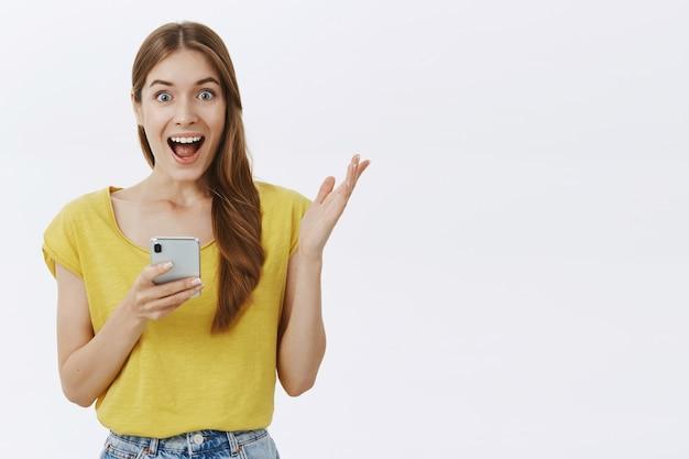 Mulher atraente usando telefone celular, enviando mensagem de texto em aplicativo ou rede social, parecendo feliz