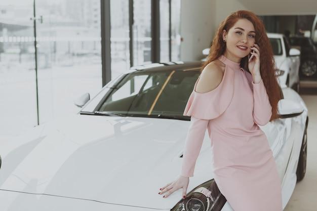 Mulher atraente usando telefone inteligente na concessionária de carros