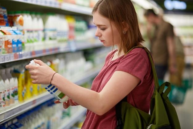 Mulher atraente vai às compras, fica no departamento de laticínios, segura a garrafa de leite, lê as informações no rótulo, verifica a data de fabricação
