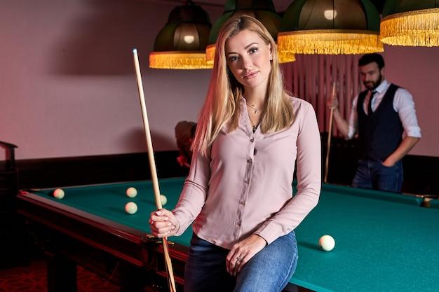 Mulher atraente veio jogar bilhar ou snooker com os amigos enquanto está sentada na mesa de bilhar verde