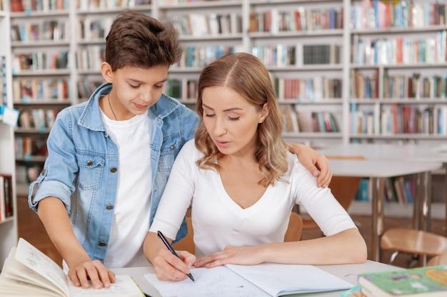 Mulher atraente, verificando os trabalhos de casa de seu filho na biblioteca.
