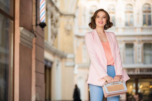 Mulher atraente vestida com roupa da moda caminhando pelas ruas de milão nas compras