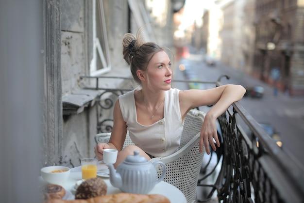 Mulher atraente, vestida de branco, sentada à mesa do café da manhã na varanda