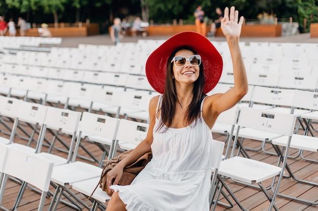Mulher atraente vestida de vestido branco, chapéu vermelho, óculos de sol, sentada no teatro ao ar livre de verão na cadeira sozinha, tendência da moda de estilo de rua de primavera, acenando com a mão