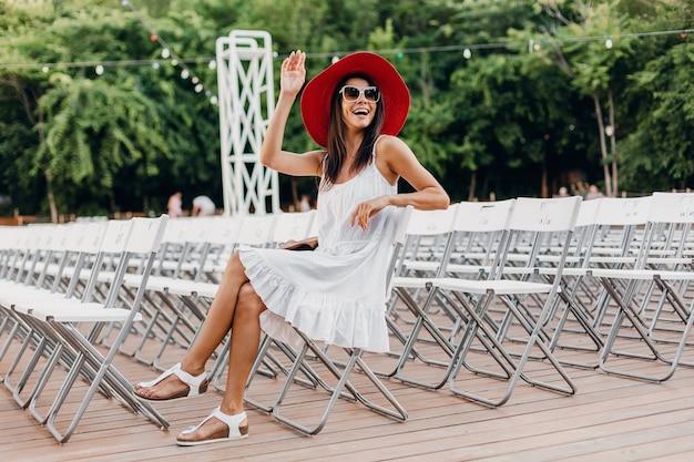 Mulher atraente vestida de vestido branco, chapéu vermelho, óculos de sol, sentada no teatro ao ar livre de verão na cadeira sozinha, tendência da moda de estilo de rua de primavera, acessórios, viajando com uma mochila, acenando com a mão