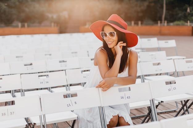 Mulher atraente vestida de vestido branco, chapéu vermelho, óculos de sol, sentada no teatro ao ar livre de verão na cadeira sozinha, tendência da moda de primavera estilo de rua, distanciamento social Foto gratuita