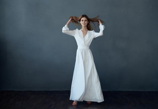 Mulher atraente vestido branco glamour luxo estúdio fundo cinza luxo. foto de alta qualidade