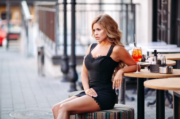 Mulher atraente vestindo vestido preto, beber cocktails e sorrindo