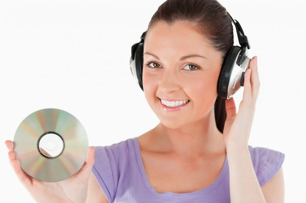Mulher atrativa com fones de ouvido com um cd enquanto está em pé