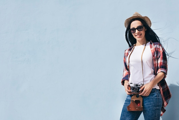 Mulher atrativa de sorriso que mantém a câmera que está contra a parede azul