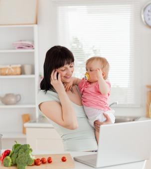 Mulher atrativa morena no telefone enquanto segurava o bebê em seus braços