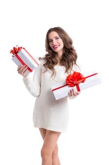 Mulher atrativa prendendo caixas brancas com as fitas brancas com presentes.