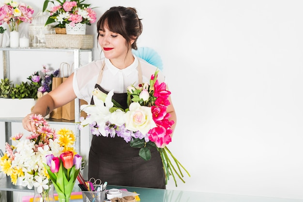 Mulher atrativa que arranja flores na loja floral