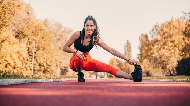 Mulher atrativa que estica antes da aptidão e do exercício