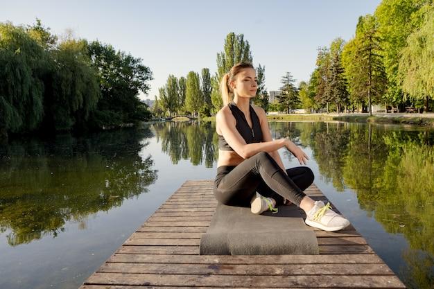 Mulher atrativa que pratica a ioga em uma esteira em um cais perto do lago na manhã