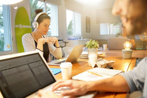 Mulher atrativa que trabalha no espaço de escritórios do co-trabalho