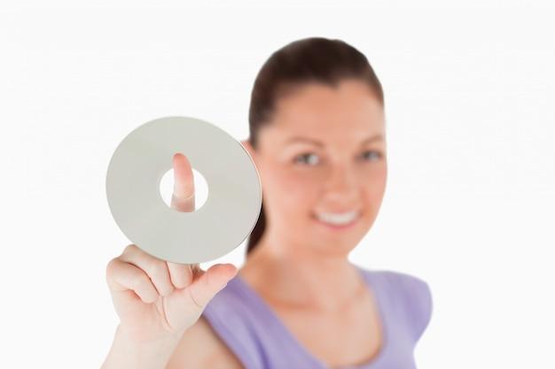 Mulher atrativa segurando um cd enquanto está de pé
