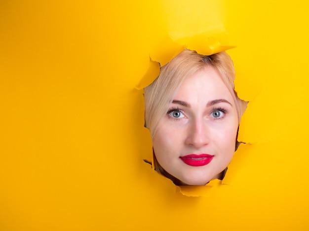 Mulher através de um buraco de papel amarelo pensando
