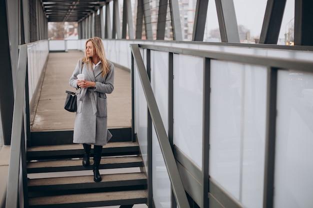 Mulher atravessando a ponte e tomando café