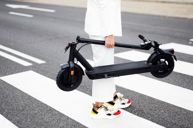 Mulher atravessando a rua com uma scooter elétrica