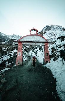 Mulher atravessando um portão de tijolos em terreno montanhoso