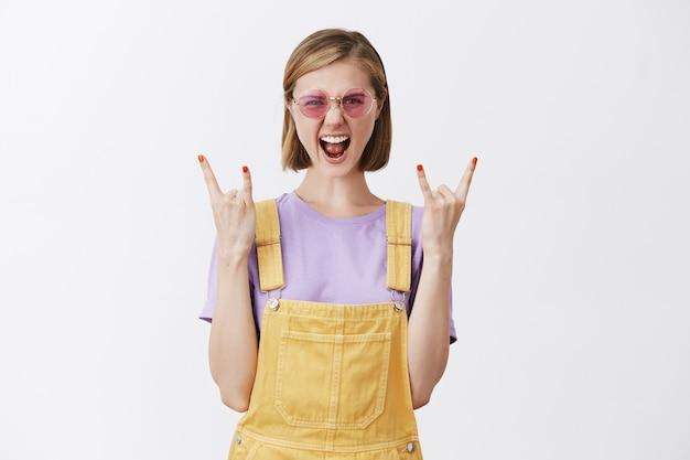 Mulher atrevida e atraente em óculos de sol elegantes e roupas de verão, mostrando gestos de rock-n-roll e gritando, sim, se divertindo