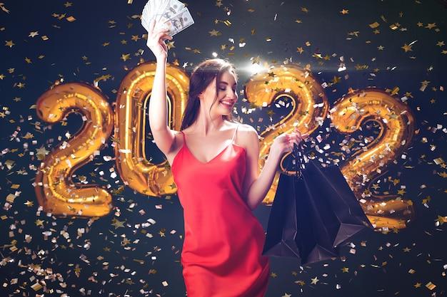 Mulher aumenta as compras de dólares em compras de ano novo. balões pretos de sexta-feira comemoram as vendas