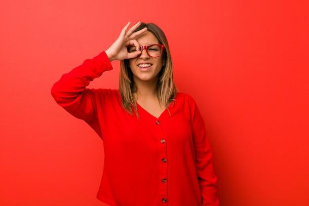 Mulher autêntica carismática autêntica nova dos povos contra uma parede excitada mantendo o gesto aprovado no olho.