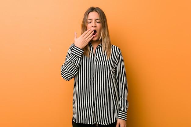 Mulher autêntica carismática autêntica nova dos povos contra uma parede que boceja mostrando um gesto cansado que cobre a boca com a mão.