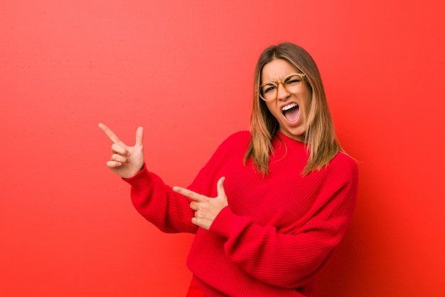 Mulher autêntica jovem carismática pessoas reais contra uma parede apontando com o dedo indicador para um espaço de cópia, expressando emoção e desejo.