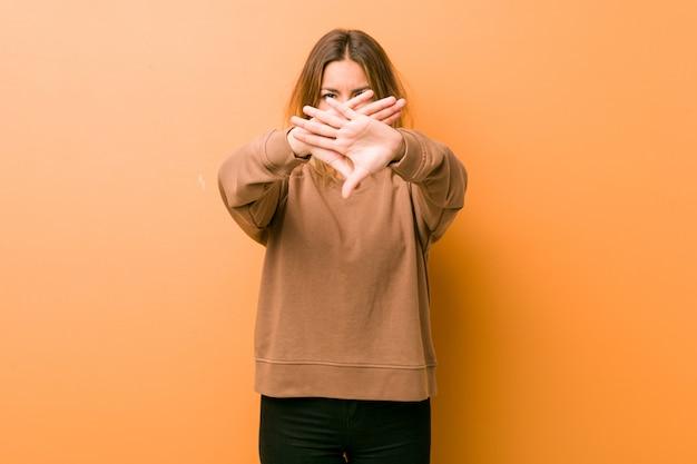 Mulher autêntica jovem carismática pessoas reais contra uma parede, fazendo um gesto de negação