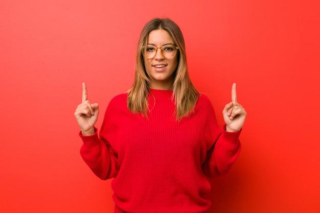 Mulher autêntica jovem carismática pessoas reais contra uma parede indica com os dois dedos da frente, mostrando um espaço em branco.