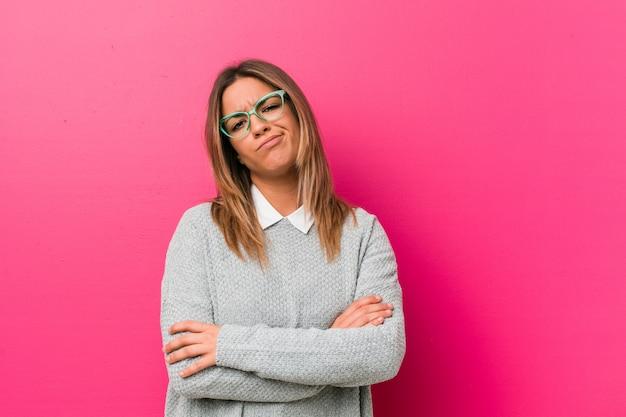 Mulher autêntica jovem carismática pessoas reais contra uma parede infeliz olhando na câmera com expressão sarcástica.