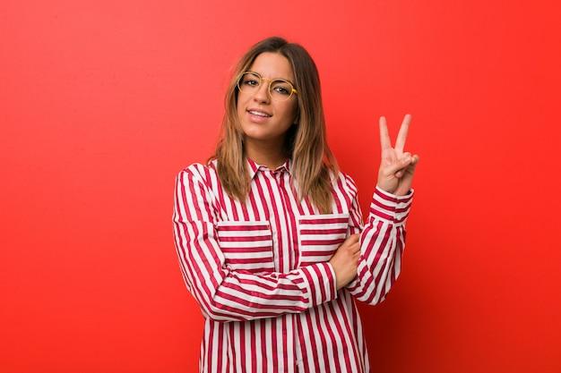 Mulher autêntica jovem carismática pessoas reais contra uma parede mostrando o número dois com os dedos.