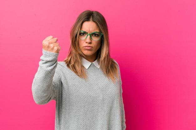Mulher autêntica jovem carismática pessoas reais, mostrando o punho, expressão facial agressiva.