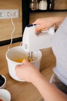 Mulher autêntica usando um mixer de mão