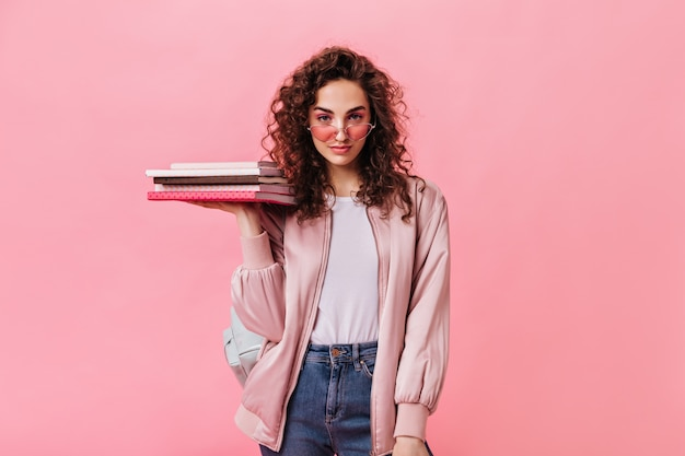 Mulher autoconfiante com roupa do dia a dia da moda segurando livros sobre fundo rosa