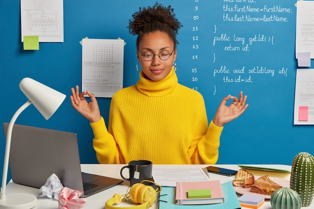 Mulher autônoma faz exercícios de ioga no local de trabalho, desfruta de uma atmosfera calma e tranquila, usa óculos redondos e macacão