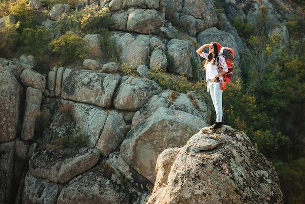 Mulher aventureira de corpo inteiro perto do desfiladeiro na rocha