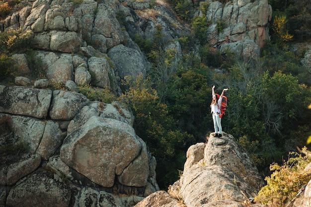 Mulher aventureira perto do cânion erguendo os braços