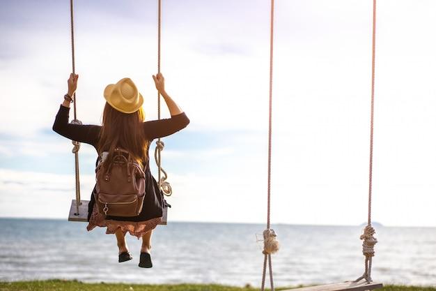 Mulher balançando em um balanço de madeira contra o mar azul. férias na praia em um resort tropical, conceito de liberdade.