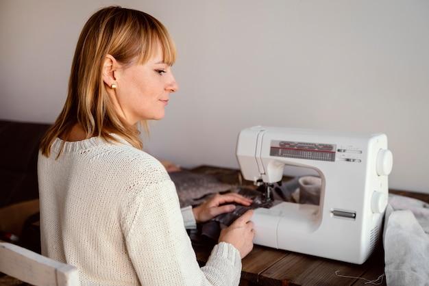 Mulher baleada por trás usando máquina de costura