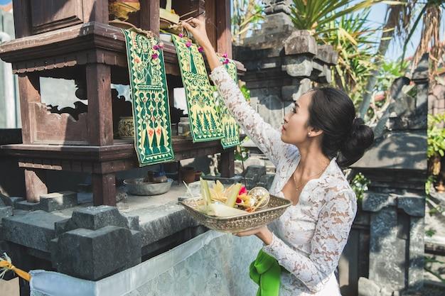 Mulher balinesa fazendo ritual oferecendo sang canang e orando