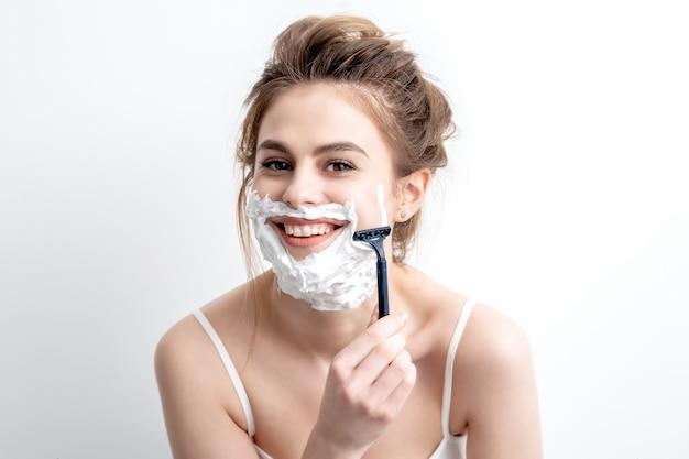 Mulher barbeando o rosto com navalha