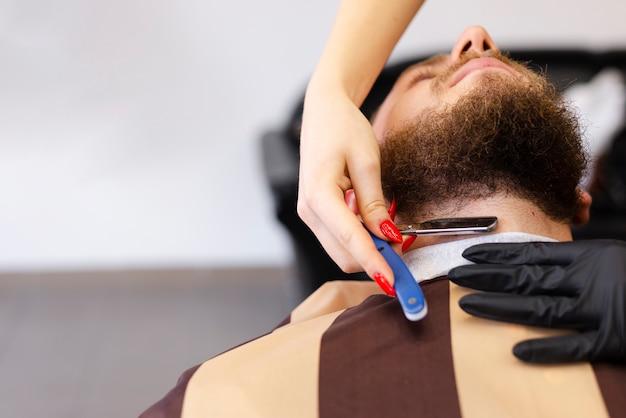 Mulher barbear a barba de um cliente com espaço de cópia