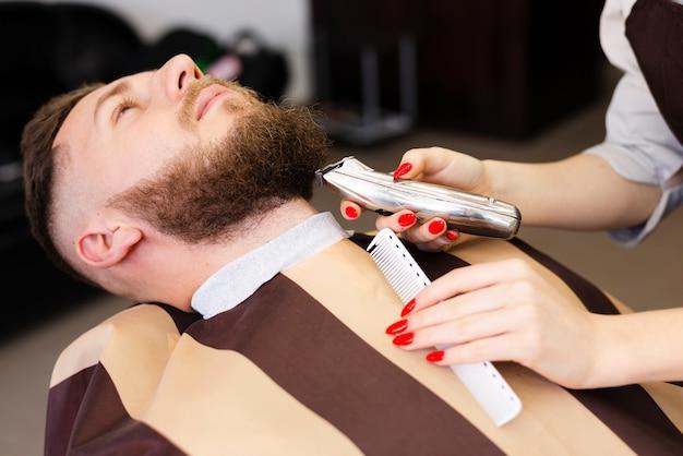 Mulher barbear o bigode do seu cliente